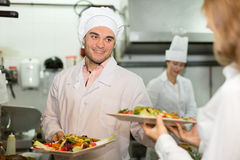 Chefs and young waiter Royalty Free Stock Images