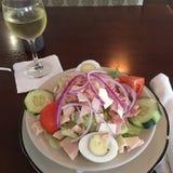 Chefsalat und ein Glas Wein Lizenzfreies Stockfoto