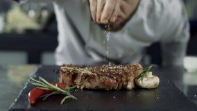 Chefsalz, das Fleisch am Bratpfanne brät Nahaufnahmemannhandsalzsteak in der Zeitlupe stock footage