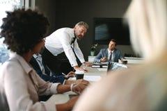 Chefstjänsteman som förklarar något till hans lag i ett möte arkivfoton