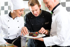 Chefteam in der Gaststätteküche mit Nachtisch lizenzfreie stockfotografie