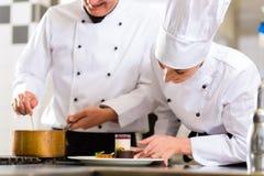 Chefteam in der Restaurantküche mit Nachtisch Lizenzfreies Stockbild