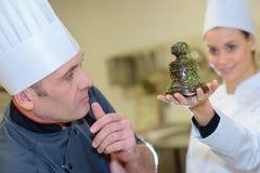 Chefteam in der Restaurantküche mit dem Nachtisch, der zusammenarbeitet lizenzfreie stockfotografie