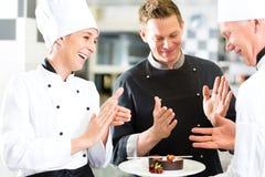 Chefteam in der Restaurantküche mit Nachtisch Stockfotografie