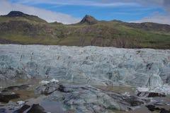 Chegada de Islândia de uma geleira no fundo verde e marrom da montanha foto de stock