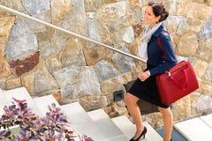 Chegada de viagem de escalada de sorriso da bagagem das escadas da mulher Fotografia de Stock Royalty Free