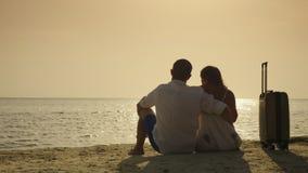 Chegada em férias Um par novo está sentando-se na areia perto de seu saco do curso Apreciando o por do sol sobre o mar vídeos de arquivo