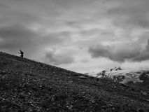CHEGET, RUSSIA - AUGUST 8, 2016: Man walking up to Mount Cheget.Walker climbs the mount Cheget. Royalty Free Stock Image