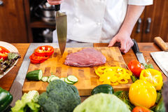 Cheif cook coooking meat and salad with fresh vegetables Royalty Free Stock Images