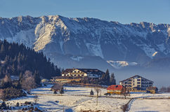 Cheile Gradistei touristic resort, Romania. Sunny winter scenery with majestic snowy Piatra Craiului mountains, chalet or lodging buildings in Cheile Gradistei Royalty Free Stock Photography