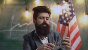 cheiro do dinheiro Empréstimos de dinheiro fáceis Pilha formal da posse do terno do homem de cédulas do dólar no fundo da bandeir filme