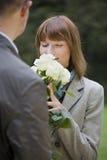 Cheiros da mulher em flores Fotografia de Stock Royalty Free