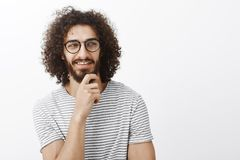 Chek it out. Intrigued attractive flirty guy in playful romantic mood, holding hand on beard, looking right and smiling. With pleased curious expression, seeing stock photo