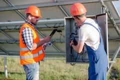 Cheking καλώδια εργαζομένων και επιστατών των ηλιακών πλαισίων Στοκ Εικόνες