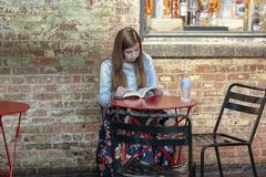 CHELSEA MARKET, NEW YORK CITY, USA - 21 July 2018: Young girl reading book in cafe royalty free stock photo