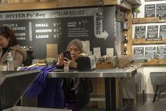 CHELSEA MARKNAD, NEW YORK CITY, USA - 14 MAJ 2018: En gammal kvinna som kontrollerar hennes smartphone i Chelsea Market royaltyfri foto