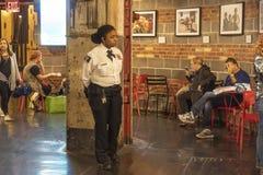 CHELSEA MARKNAD, NEW YORK CITY, USA - 14 MAJ 2018: Kvinnlig polis i Chelsea Market royaltyfri foto