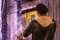 CHELSEA rynek, MIASTO NOWY JORK, usa - 14 2018 MAJ: Młody człowiek bierze obrazki na jego smartphone w Chelsea rynku zdjęcie stock