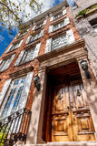 Chelsea townhouse, Manhattan, New York City. Four-storey townhouse in Chelsea, Manhattan. Typical NYC townhouse architecture with wooden entrance door and brick Royalty Free Stock Photo