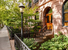 Chelsea tree-filled street and its townhouses and. Peaceful view of a street in Chelsea, NYC. Urban photography of terraced townhouses with their front yards Royalty Free Stock Photography