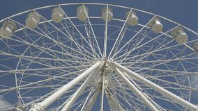 Cheltenham, United Kingdom. June 22, 2019 - White ferris wheel of the amusement park in the blue sky background. Cheltenham, United Kingdom. June 22, 2019 stock footage