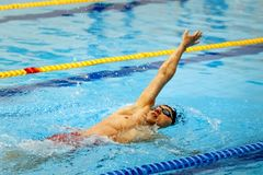 Male swimmer swimming backstroke in pool. Chelyabinsk, Russia - March 13, 2018: male swimmer swimming backstroke in pool during Championship Ural Federal Royalty Free Stock Photos