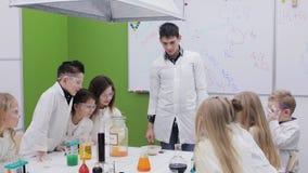 Chemia nauczyciela przedstawienia eksperymentują dzieci w klasie zbiory