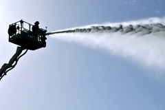 Chemical and Biological War. KIRYAT MALAKI - DECEMBER 2: Silhouette of Firefighter on a ladder spray water from a hose during an exersice with a scenario that Royalty Free Stock Image