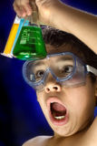 Chemical boy. A child amazed watching a chemical experiment in test tubes Stock Photography