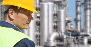 Chemical Engineer. Close up of an engineer wearing a safety vest, blue coveralls, and a hard hat in front of a petrochemical plant