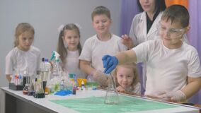 Chemical experiments for children. A woman adds ingredients to a flask for chemical experiments. A column of smoke rises