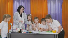Chemical experiments for children. Woman pours a green substance into a clear glass. Children are surprised. The boy