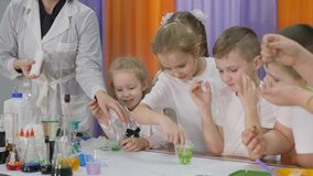 Chemical experiments for children. Woman pours a green substance into a clear glass. Children are surprised. The girl is