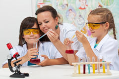 Chemical experiments in elementary school. Kids helped by teacher in science class Stock Photo