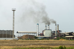 Chemical factory with smoke stack. Black on the sky Stock Images