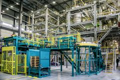 Chemical factory. Thermoplastic production line and packing machinery in large area of industrial hall. Chemical factory. Thermoplastic production line royalty free stock photo
