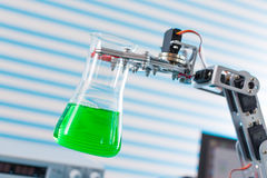 Chemical flask in robot arm Stock Photos