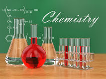 Chemical flasks and blackboard with formulas. Stock Images