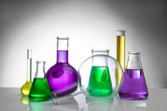 Chemical flasks and test-tube. On color background royalty free stock images