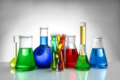 Chemical flasks and test-tubes on background. Chemical flasks and test-tubes on color background royalty free stock images