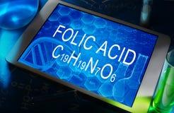 The chemical formula of Folic acid. The chemical formula of  Folic acid on a tablet with test tubes Royalty Free Stock Photography