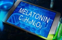 The chemical formula of melatonin. The chemical formula of  melatonin on a tablet with test tubes Royalty Free Stock Photo