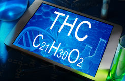 The chemical formula of THC. The chemical formula of  THC on a tablet with test tubes Royalty Free Stock Images