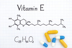 Chemical formula of Vitamin E and pills. Royalty Free Stock Images