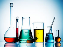 Chemical glassware. Silhouetted beakers, test tubes and other chemical glassware items with colorful liquids Royalty Free Stock Photography