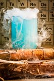 Chemical lab with color beakers in school. On old wooden table Royalty Free Stock Photos