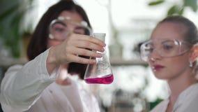 chemical laboratorium Två unga kvinnor som ser flaskan med rosa flytande i den och att utvärdera resultatet lager videofilmer