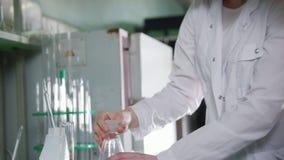 chemical laboratorium Två unga kvinnor som ser flaskan med rosa flytande i den och puttint det på tabellen stock video