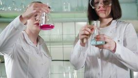 chemical laboratorium Två unga labbtekniker som gör experiment med flytande i flaskor stock video