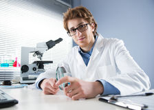 Chemical laboratory technician holding magnifier. Chemical laboratory technician smiling and holding a magnifier with equipment on background Stock Image